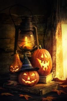 Halloweenowe dynie i latarnia w starym domu przy oknie, w którym świeci księżyc.