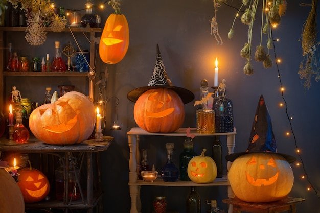 Halloweenowe dynie ze światłami i płonącymi świecami i magicznymi miksturami w domu czarownicy