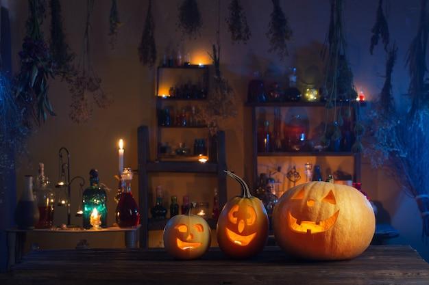 Halloweenowe dynie ze świecami i magicznymi miksturami w nocy wewnątrz
