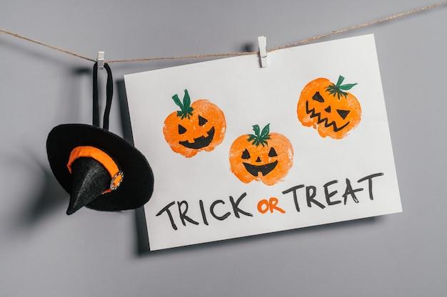 Halloweenowe dyniowe jabłko drukuje rysunek wiszące na linie na szarej ścianie z napisem treat or treat i kapeluszem wiedźmy