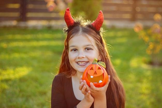 Halloweenowe dzieci. portret śmiesznej dziewczyny z czerwonymi rogami chochlika na głowie, trzymając w rękach lampę z dyni.