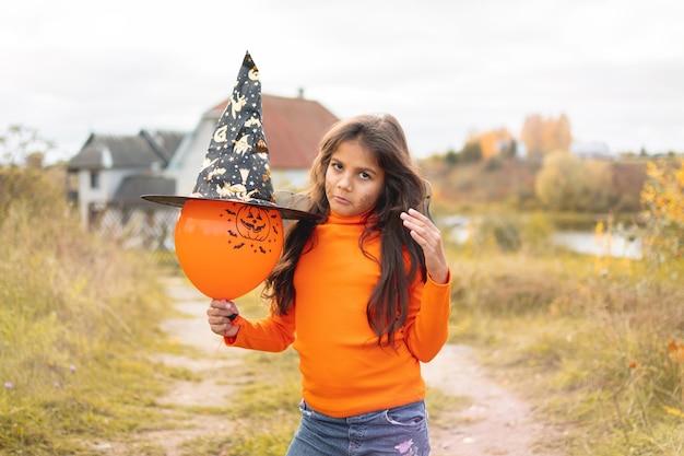 Halloweenowe dzieci. portret smutna dziewczyna z brązowymi włosami w kapeluszu czarownicy. śmieszne dzieci w kostiumach karnawałowych na zewnątrz.
