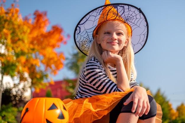 Halloweenowe dzieci. portret uśmiechnięta dziewczyna w kapeluszu czarownicy z dyniowym cukierkiem wiaderkiem. śmieszne dzieciaki w karnawale