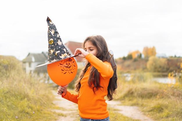 Halloweenowe dzieci. portret uśmiechnięta dziewczyna z brązowymi włosami w kapeluszu czarownicy. śmieszne dzieci w kostiumach karnawałowych na zewnątrz.