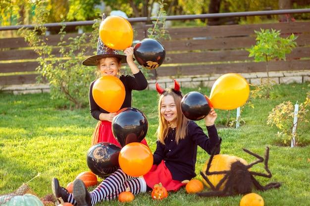 Halloweenowe dzieci. śmieszne dziewczyny w karnawałowych strojach siedzą na trawie z dyniami i wielkim czarnym pająkiem na świeżym powietrzu i trzymają w rękach czarno-pomarańczowe balony.
