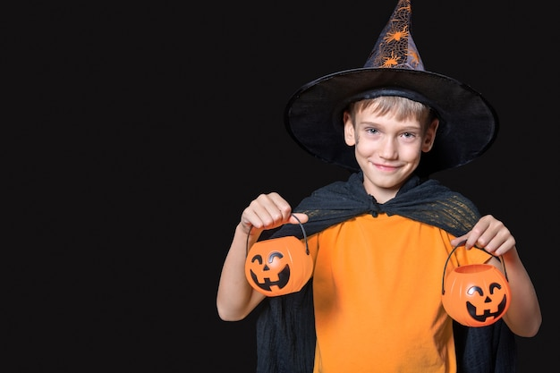 Halloweenowe dzieciaki. chłopiec w kapeluszu czarodzieja i pomarańczowy t-shirt, trzymając wiadra słodyczy w kształcie dyni halloween na białym tle na czarnym tle. gotowy na świąteczny smakołyk.