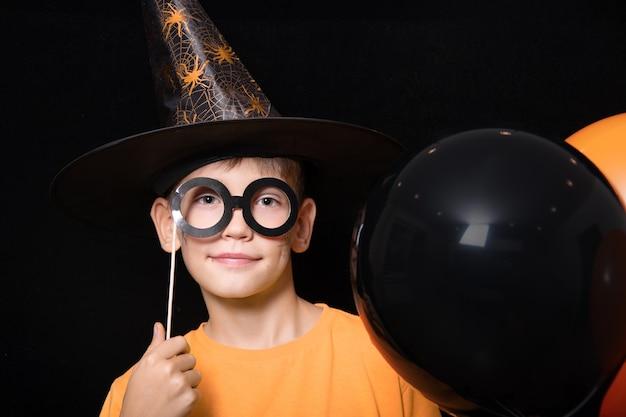 Halloweenowe dzieciaki. chłopiec w kapeluszu czarodzieja iw masce czarnych okularów trzymający pomarańczowe i czarne balony na czarnym tle. gotowy na świąteczny smakołyk.