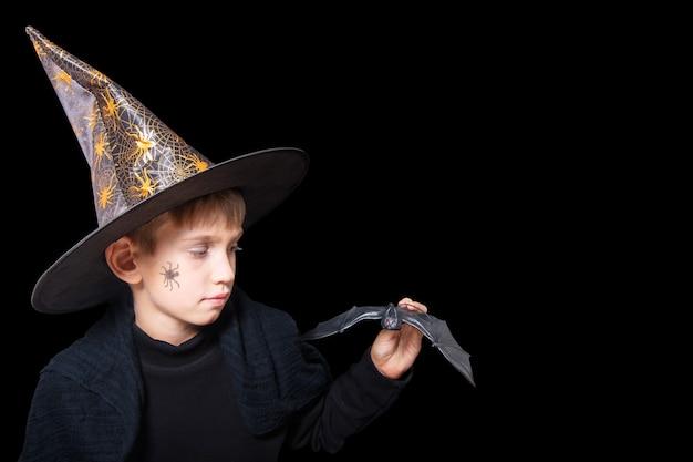 Halloweenowe dzieciaki. chłopiec w kapeluszu czarodzieja iz namalowanym pająkiem na policzku, trzymający czarnego nietoperza halloween, by przestraszyć kogoś odizolowanego na czarnym tle. gotowy na świąteczny smakołyk.