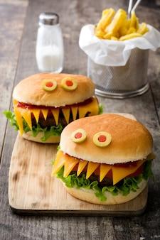 Halloweenowe hamburgerów potwory z frytkami na drewnianym stole