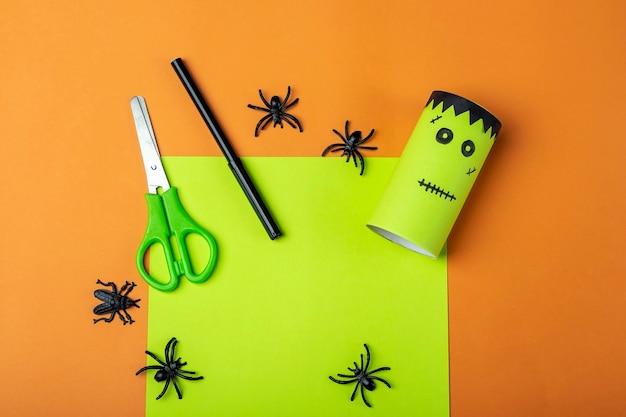 Halloweenowe majsterkowanie i kreatywność dzieci. instrukcja krok po kroku: robienie zielonego potwora frankensteina z tuby na papier toaletowy. krok 2 zakończył pracę. dziecięce rzemiosło. ekologiczny recykling.