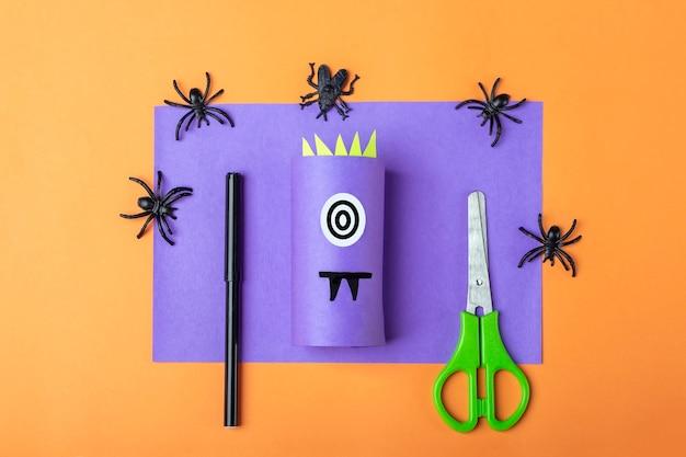 Halloweenowe majsterkowanie i kreatywność dzieci. instrukcja krok po kroku: zrobić fioletowego potwora z tuby papieru toaletowego. krok 2 zakończył pracę. dziecięce rzemiosło. ekologiczny recykling.