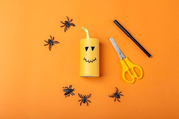 Halloweenowe majsterkowanie i kreatywność dzieci. instrukcja krok po kroku: zrobienie pomarańczowej dyni potwora z tuby papieru toaletowego. krok 2 zakończył pracę. dziecięce rzemiosło. ekologiczny recykling.
