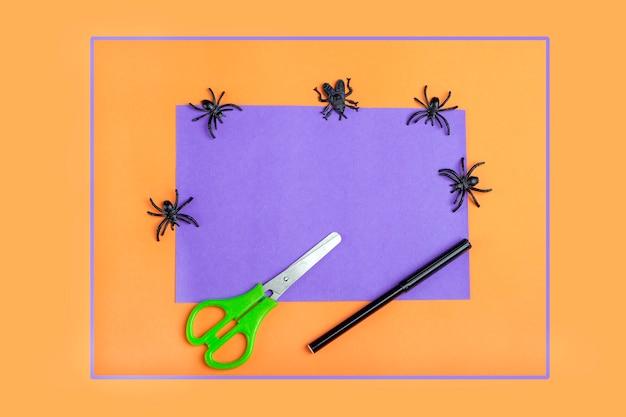 Halloweenowe majsterkowanie i kreatywność dzieci. narzędzia do przygotowania: tuba na papier toaletowy, nożyczki, kolorowy papier do robienia potwora dekoracyjnego. dzieci craft ekologiczny recykling.