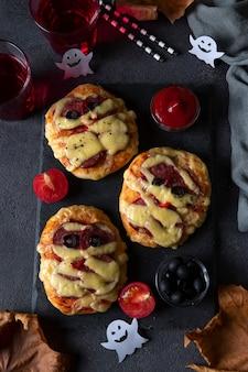 Halloweenowe mumie mini pizzy z kiełbasą i serem, podawane z czarnymi oliwkami, ketchupem i napojami na ciemnej desce, widok z góry