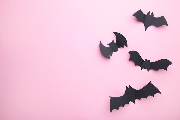 Halloweenowe nietoperze na pastelowym różowym tle. halloween, rama