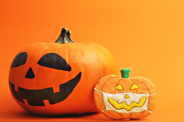 Halloweenowe pierniczki na pomarańczowym tlejack olantern i pyszne ciastko na halloween