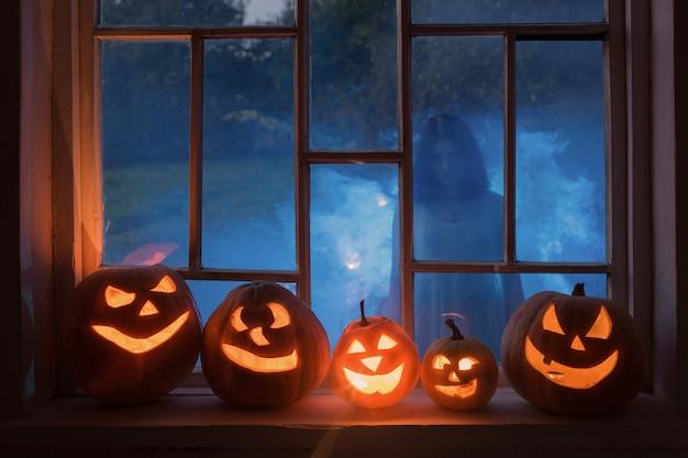 Halloweenowe pompy na parapecie z duchem na zewnątrz okna