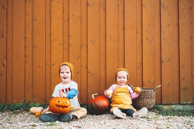 Halloweenowe przyjęcie dla dzieci urocze dzieci z dyniami na drewnianej stodole z miejscem na kopię