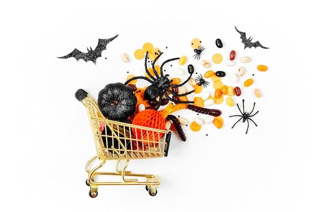 Halloweenowe smakołyki w koszyku na białym tle. cukierek albo psikus, koncepcja na halloween. płaski układanie, widok z góry