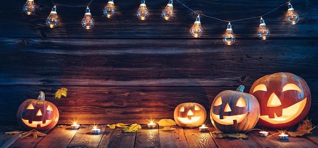 Halloweenowe tło ozdobione lampkami dyni z latarnią i świecami drewniana ściana z kopiami...