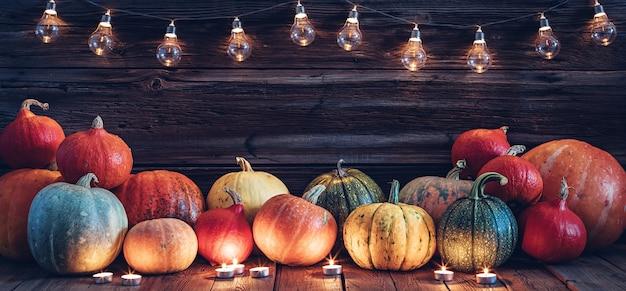 Halloweenowe tło ozdobione światłami dyni i świecami drewnianą ścianą z miejscem na kopię
