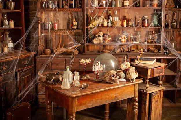 Halloweenowe tło półki z narzędziami do alchemii butelka z pajęczyną czaszki z zatrutymi świecami miejsce pracy wiedźmina straszny pokój