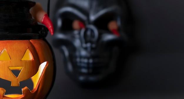 Halloweenowe tło świecąca dynia i czarna czaszka na ciemnym tle ludzkie palce z długim...