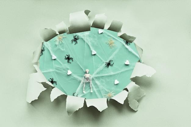Halloweenowe tło w kolorze zielonym mięty w papierowym otworze