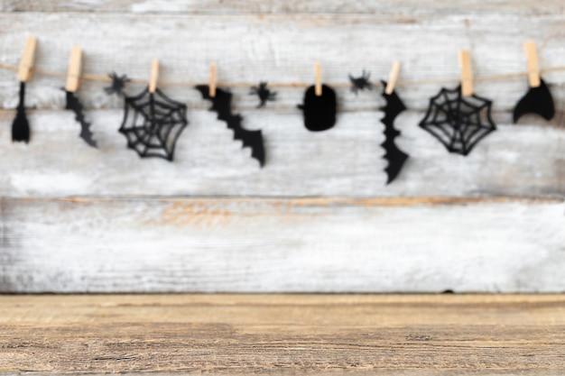 Halloweenowe tło z niewyraźną girlandą czarnych akcesoriów i skoncentrowaną drewnianą powierzchnią