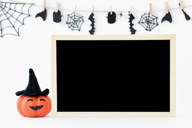 Halloweenowe tło z pomarańczową dynią halloween i czarną tablicą