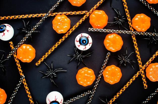 Halloweenowe tło z wieloma dyniami, cukierkami i pająkami na czarnych, jesiennych wakacjach