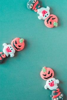 Halloweenowi cukierki układali w naprzemiennym wzorze na barwionym tle