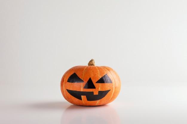 Halloweenowy bani głowy dźwigarki o lampion z uśmiechem odizolowywającym na bielu.