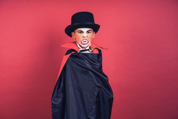 Halloweenowy chłopiec wampir macha swoim czarnym, czerwonym płaszczem z rękami otoczonymi na czerwonym tle studia. makijaż dla dzieci wampirów.