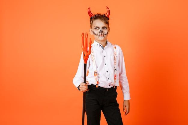 Halloweenowy chłopiec z rogami diabła z widłami na tle pomarańczowej ściany. wysokiej jakości zdjęcie
