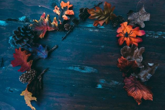 Halloweenowy drewniany stół z kolorowymi liśćmi
