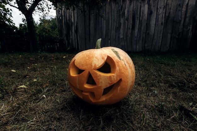 Halloweenowy dyniowy lampion z płonącymi świeczkami na ciemnym tle