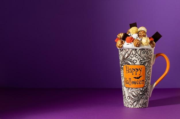 Halloweenowy freak shake w wysokim kubku na fioletowym tle z cieniem. bita śmietana z glazurowanym popcornem, kolorową pianką i czekoladą. tło halloween z miejsca na kopię.