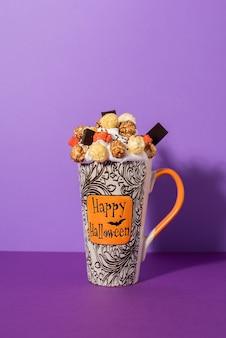 Halloweenowy freak shake w wysokim kubku na fioletowym tle z cieniem. bita śmietana z glazurowanym popcornem, kolorową pianką i czekoladą.