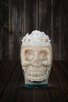 Halloweenowy koktajl w czara czaszce na drewnianej półce.