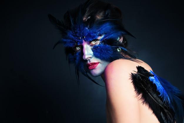 Halloweenowy makijaż. fantasy bird woman z artystycznym makijażem na niebieskim tle i kopią miejsca na tekst