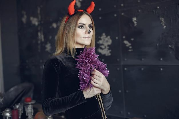 Halloweenowy makijaż piękna kobieta z blond fryzurą. modelka dziewczyna w czarnym stroju. motyw halloween.