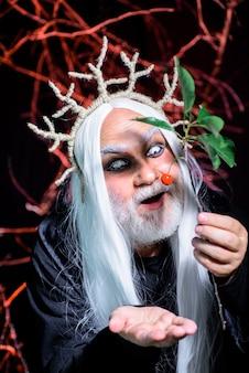Halloweenowy mężczyzna brodaty mężczyzna gotowy na imprezowy horror, człowiek stoi przed halloweenową dekoracją i przerażającą koncepcją