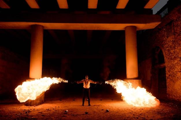 Halloweenowy mężczyzna w kostiumu z miotaczem ognia w jego rękach. diabelski makijaż na twarzy