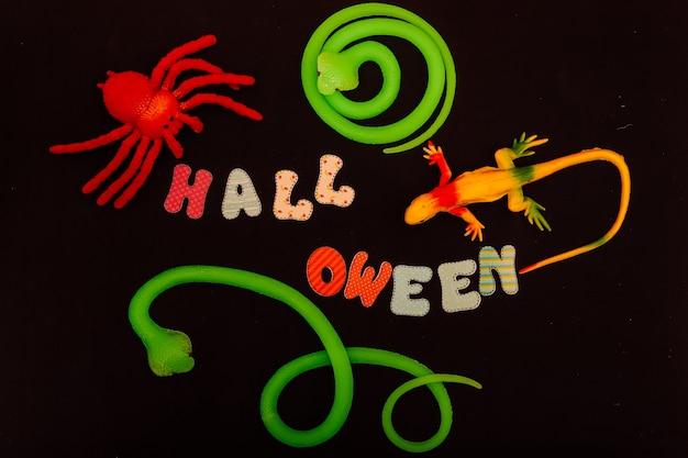 Halloweenowy napis wokół jaszczurki węża i pająka na czarnym stole