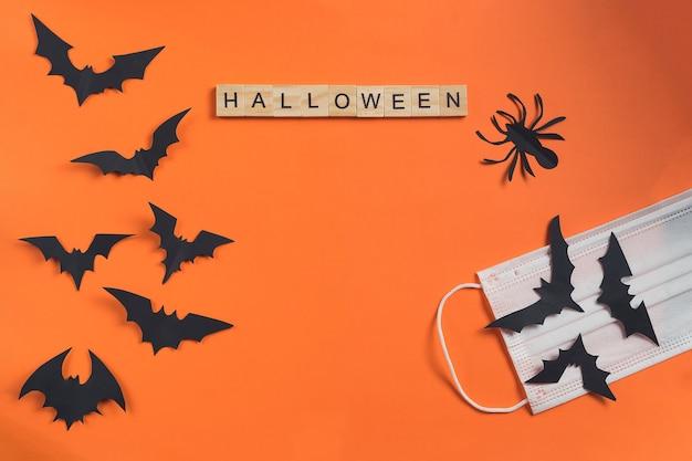 Halloweenowy napis wykonany z drewnianych kostek i nietoperzy wyciętych z czarnego papieru na pomarańczowym tle z ochronną maseczką medyczną. wakacje w czasie kwarantanny. styl cięcia papieru. flatlay, kopia przestrzeń