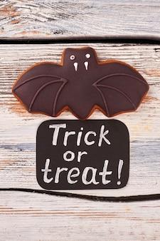 Halloweenowy nietoperz cookie na drewnianym tle.