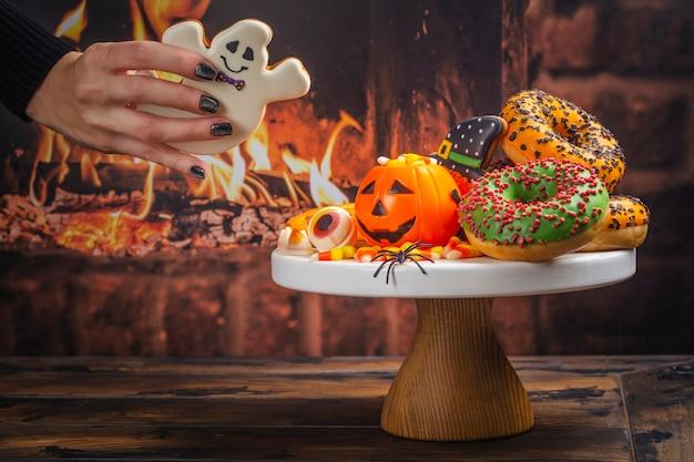 Halloweenowy stół dla dzieci z cukierkami, ciasteczkami imbirowymi i upiornymi pączkami