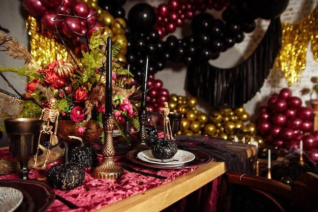 Halloweenowy stół ozdobiony przerażającymi ornamentami, takimi jak czaszka, czarny nietoperz