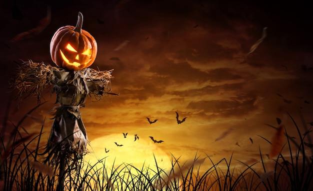 Halloweenowy strach na wróble dyniowy na szerokim polu z księżycem w straszną noc
